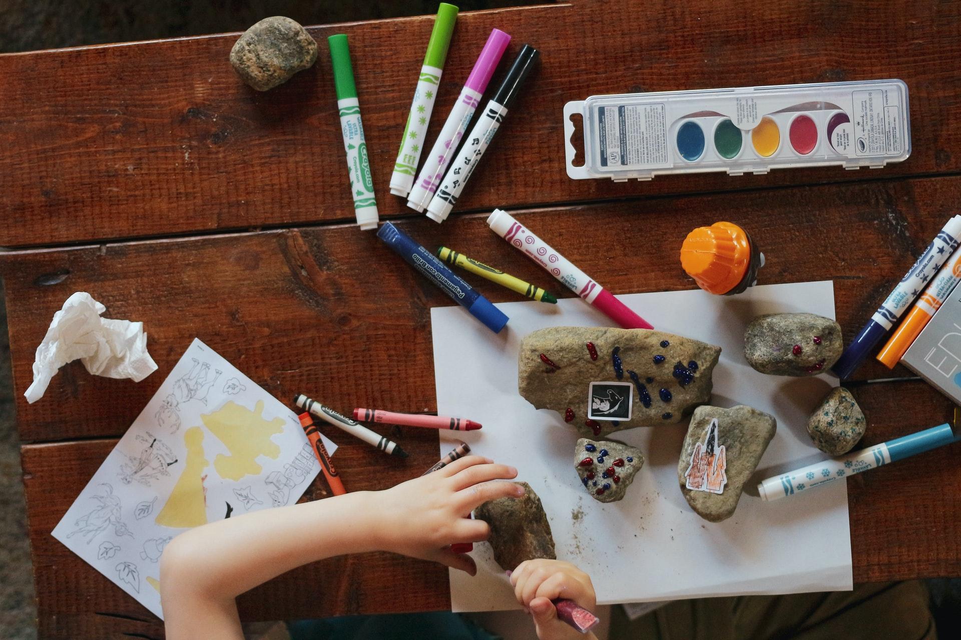 enfant sur une table avec des crayons peinture et cailloux